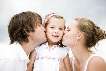 Parents kissing daughter