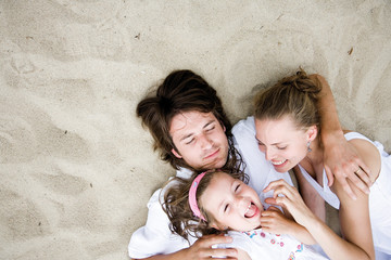 Parents with daughter lying on sand, overhead view