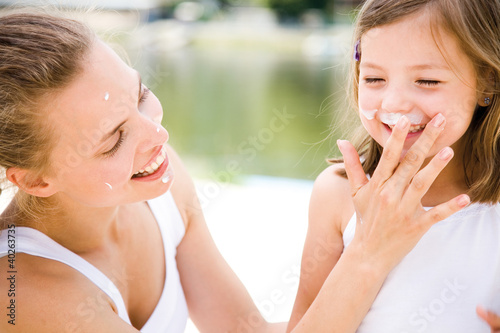 Mother applying cream on daughter's face