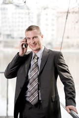 Businessman using mobile phone, smiling, portrait