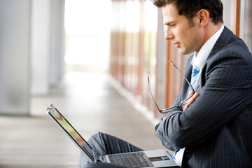 Businessman looking at laptop, side view