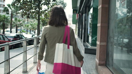 Woman with shopping bags walking in the city, slow motion