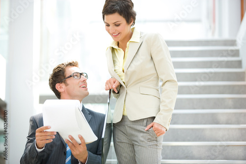 Business people holding document, smiling