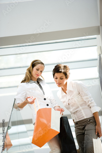 Businesswoman holding bag while other looking in it
