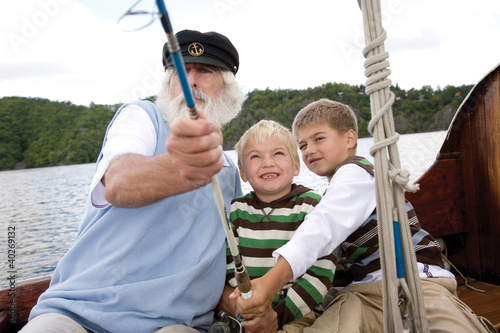 Grandfather with grandsons holding fishing rod