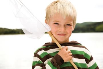 Boy holding fishing net, smiling, portrait