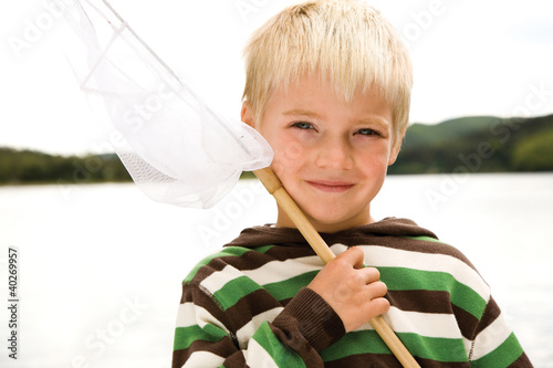 Boy holding fishing net, smiling, portrait