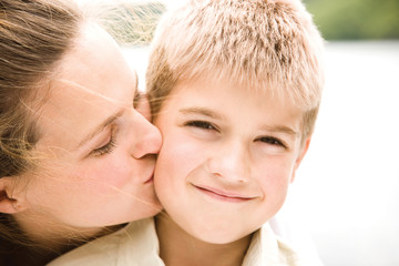 Mother kissing son, smiling, portrait