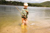Boy holding fishing net in water, portrait