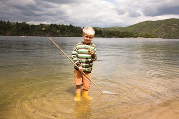 Boy holding fishing net in water