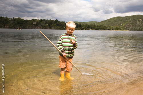 Boy holding fishing net in water