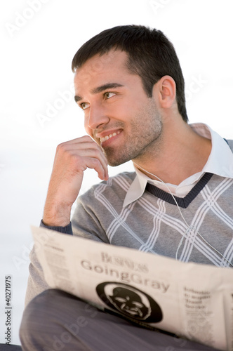 Young man listening music while holding newspaper