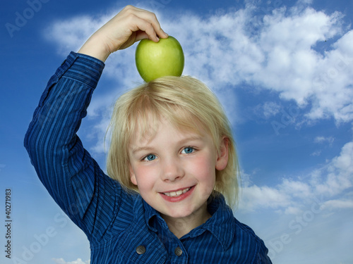 Cute girl balances her green apple eaten during break