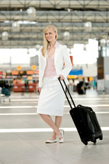 Young woman holding luggage cart, portrait