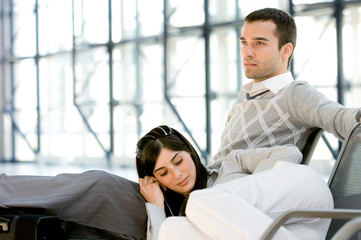 Young man and woman relaxing at waiting room