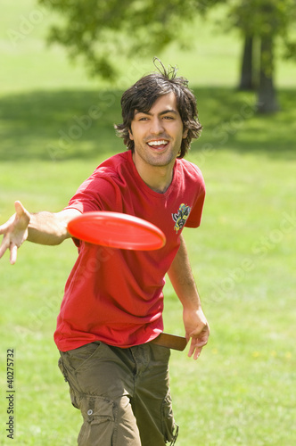 Young man playing with plastic disc on park
