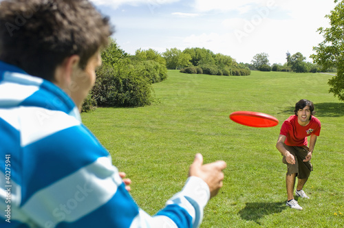 Friends playing with plastic disc on park