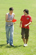 Two young men with plastic disc on park