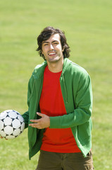 Young man holding soccer ball in park, portrait
