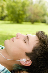 Young man wearing earphones lying on grass, close-up