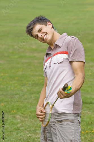 Young man holding badminton racquet in park