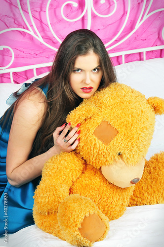 beautiful woman sitting on a bed with teddy bear