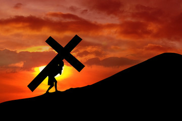 Christian background - man carrying a cross up hill