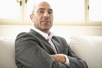 Businessman sitting on sofa with arms crossed, portrait