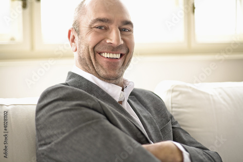 Businessman sitting on sofa with arms crossed, smiling, portrait