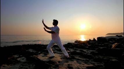 Man practicing Tai Chi at sunrise on the beach
