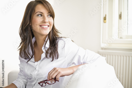 Young woman sitting on sofa, holding spectacles