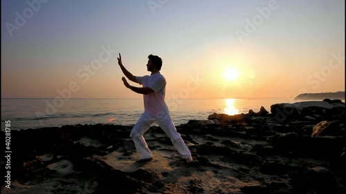 Man practicing Tai Chi at sunrise on the beach