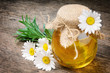 Glass pot of honey with daisies
