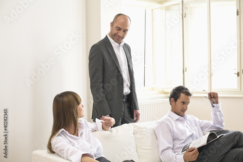 Businesspeople sitting on sofa while colleague standing