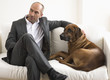Businessman sitting on sofa with dog