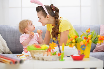 Mother and baby playing with Easter eggs