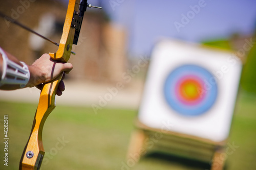Archer who holds his bow aims at target