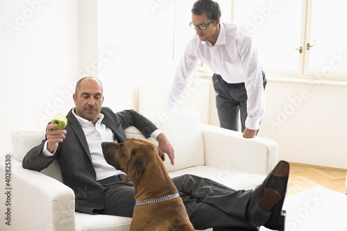 Businessman sitting on sofa, showing apple to dog