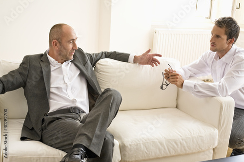 Mid adult man persuading mature man