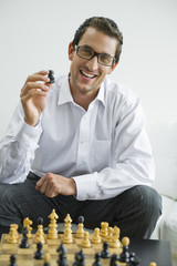 Mid adult holding chess piece, smiling, portrait