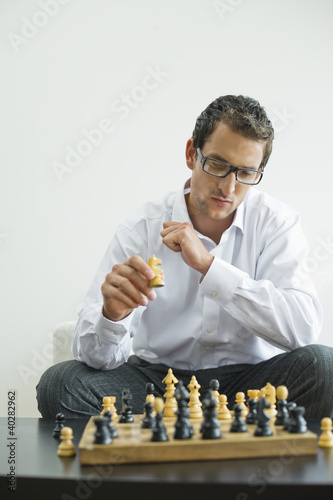 Mid adult man playing chess
