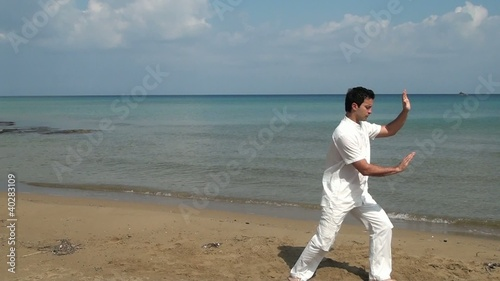 Man practicing Tai Chion the beach