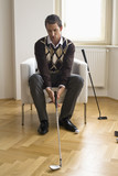 Mid adult man holding golf club, sitting on chair