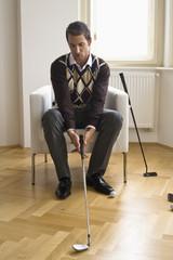 Mid adult man holding golf club, sitting on chair