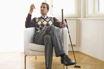 Mid adult man sitting on chair, looking at golf ball