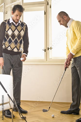 Men holding golf clubs
