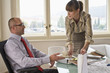 Business woman giving tea cup to business man in office