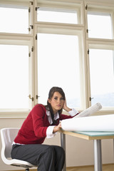 Businesswoman sitting by table with blue print