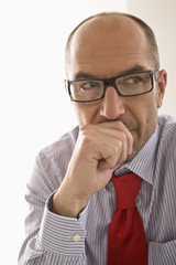 Businessman contemplating in office, close-up