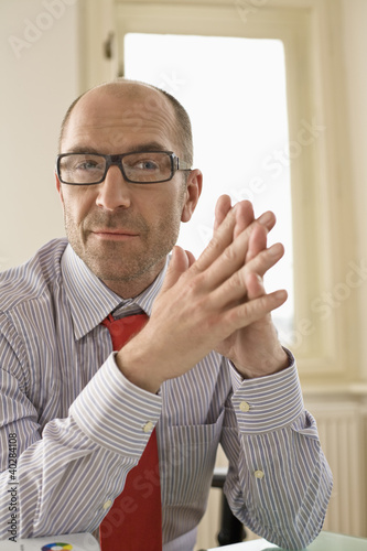 Businessman sitting with hands clasped in office